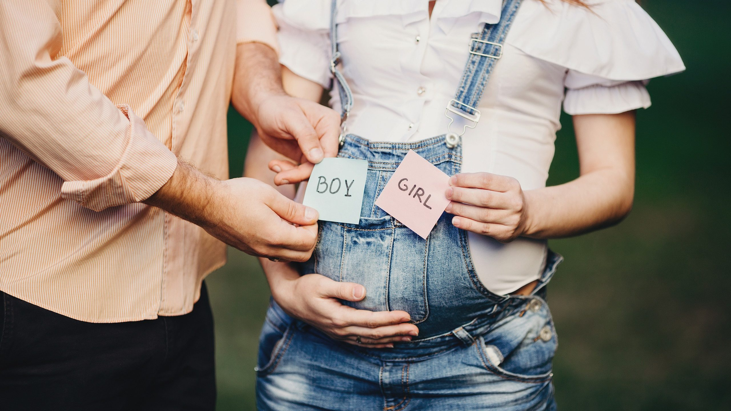 Male and female hands with BOY and GIRL cards near pregnant woman belly. Pregnancy, motherhood, fatherhood, twins, son, daughter concept.